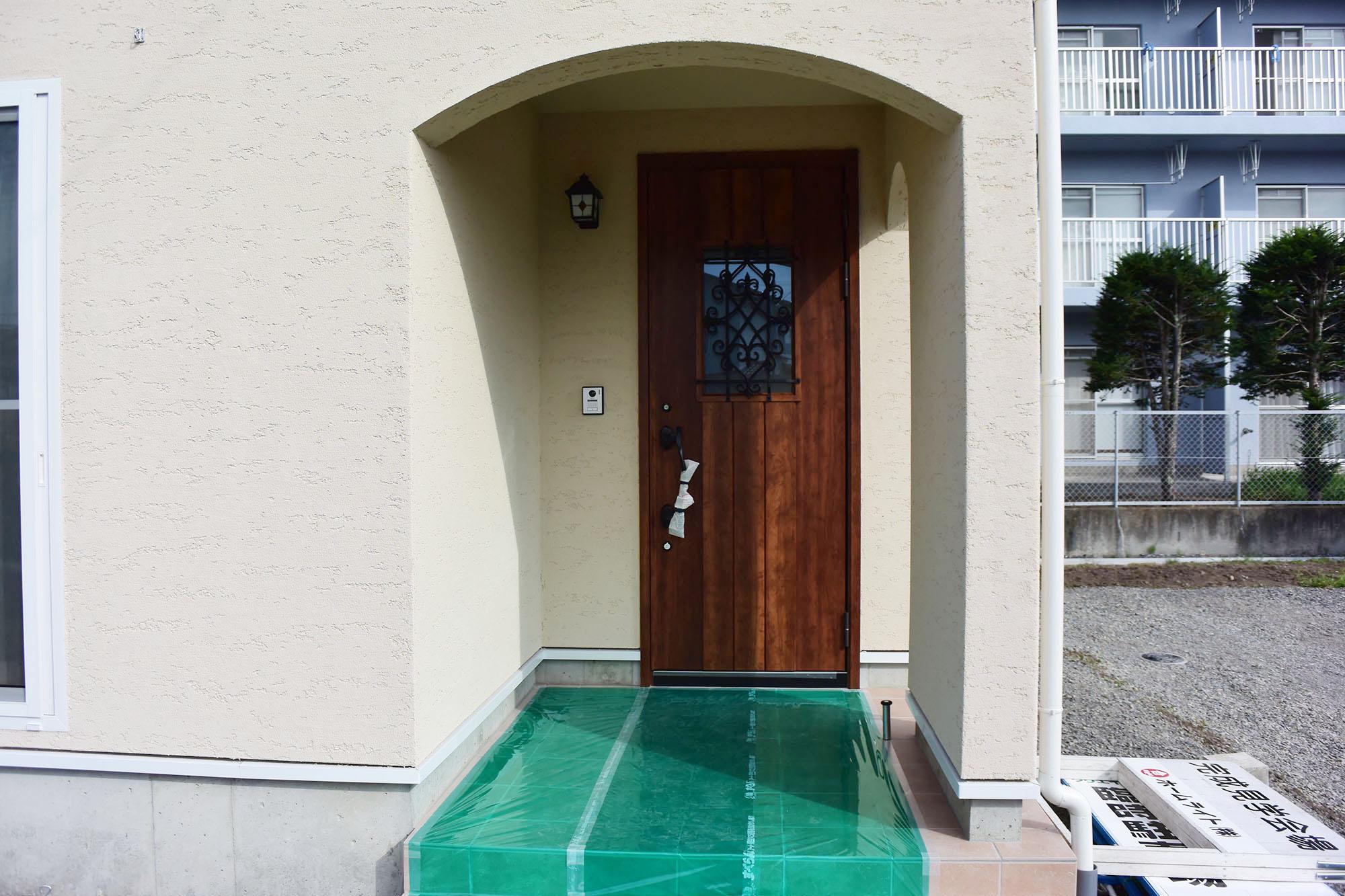 塗り壁の外壁にマッチしたお洒落で重厚な玄関ポーチ。