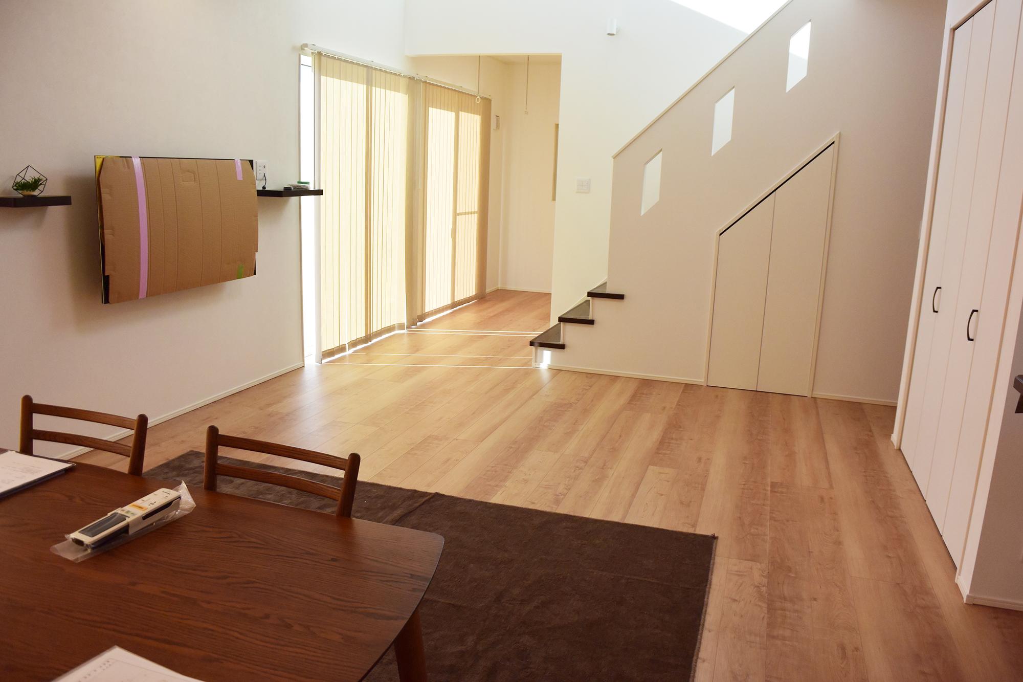 リビングでは壁掛けの大型テレビでくつろげます。階段の向こうにはサンルームが広がります。