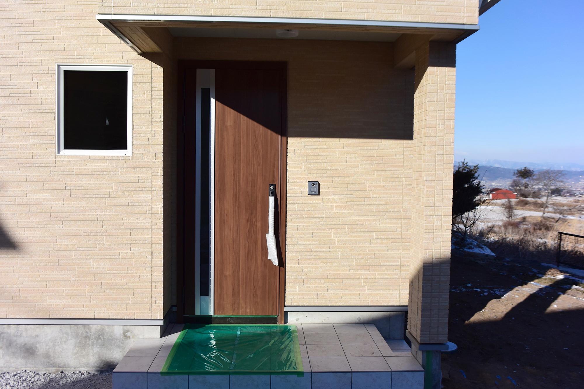 明るく広がる玄関ポーチ。外壁と玄関扉が実にマッチしていてとても良いセンスを感じます。