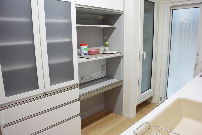 システムキッチンとお揃いの色合いのおしゃれな食器棚。