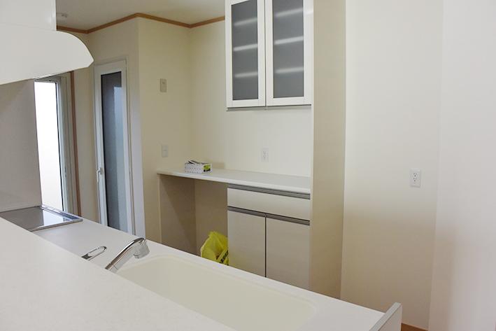 システムキッチンとお揃いの食器棚。奥には大きなホームライトオリジナルの冷温庫。